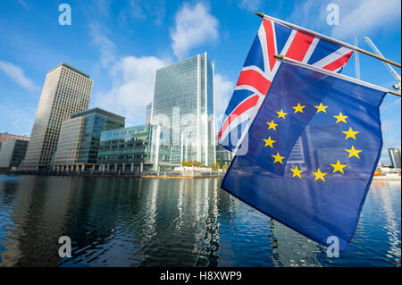 European Union and Union Jack flags flying above modern business towers of the financial center of Canary Wharf - Stock Photo