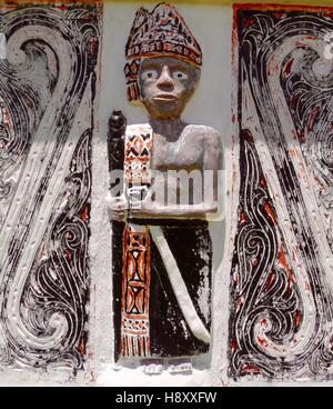 Carving of figure of Batak hunter with traditional colours and design of that ethnic group from the Indonesian island - Stock Photo
