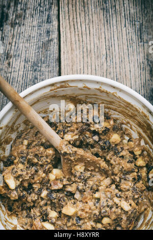 Christmas pudding mixture in a bowl with a wooden spoon. Stir up sunday - Stock Photo