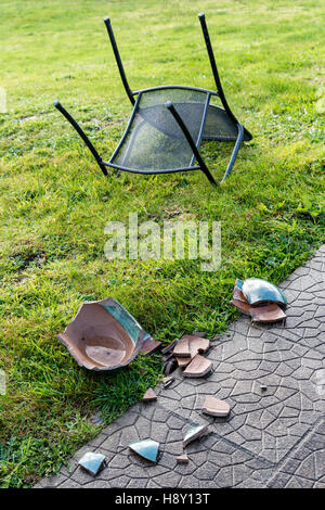 Blown Over Garden Table And Chairs And Broken Ceramic Plant Pot, Caused By  High Winds