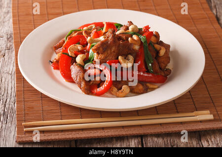 Thai Food: Fried chicken with vegetables and cashew nuts closeup on a plate on the table. horizontal - Stock Photo