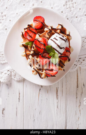 Tasty waffles with strawberries, whipped cream and chocolate frosting close up. Vertical view from above - Stock Photo