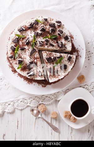 Delicious cheesecake with chocolate cookies closeup on a plate. Vertical view from above - Stock Photo