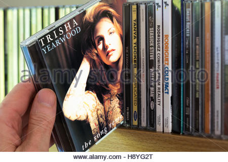The Song Remembers When, Trisha Yearwood CD being chosen from a shelf of other CD's - Stock Photo