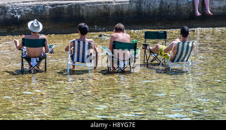 The boys sitting in the shallows on chairs - Stock Photo