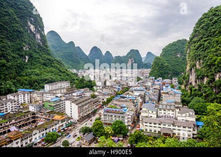 YANGSHUO, CHINA - JUNE 12: View over skyline of Yangshuo surrounded with recognizable karst landscape. Karst mountains - Stock Photo