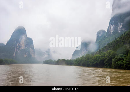 Li river with misty clouds and fog surrounded by famous karst mountains, Guangxi Zhuang, China - Stock Photo