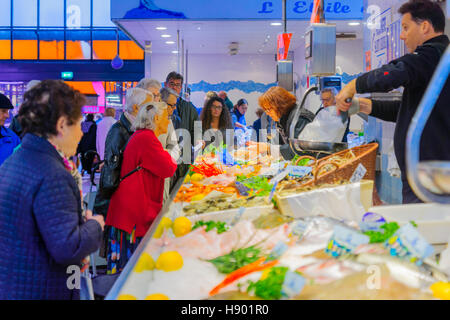 DIJON, FRANCE - OCTOBER 14, 2016: Market scene with various fish and seafood, sellers and shoppers, in Dijon, Burgundy, - Stock Photo