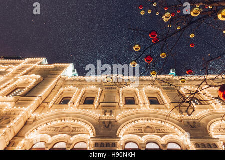 Christmas decorations in front of illuminated facade of the Central Department Store GUM on the Red Square in Moscow, - Stock Photo