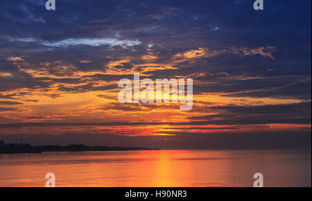 Scene of golden hour sky with dark cloud reflecting on flat water surface with orange light before sunrise. - Stock Photo
