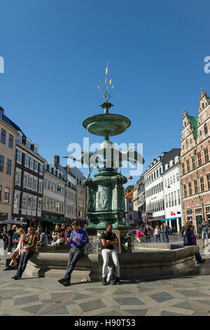 People are sitting on the Amagertorv Square and Stork Fountain in Copenhagen, Denmark - Stock Photo
