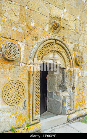 The entrance to Tsminda Sameba (Holy Trinity) Church decorated with the medieval rosette carved patterns, Gergeti, - Stock Photo