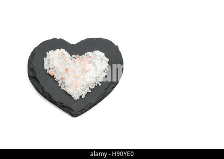Pink salt crystals on black heart shaped slate - Stock Photo