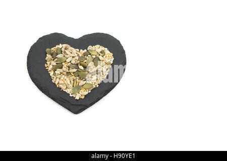 Mixed seeds on heart-shaped black slate - Stock Photo
