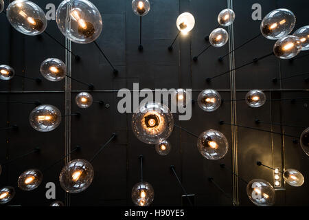 Bottom view of light bulbs background over dark wall - Stock Photo