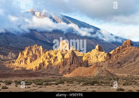 Rocky mountain tops glowing in sunset light at the foot of volcano El Teide covered with low clouds in Tenerife - Stock Photo