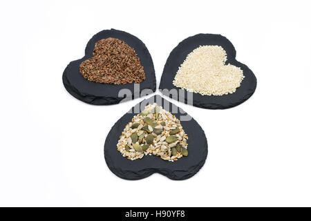 Trio of seeds, sunflower, linseed, flaxseed, pumpkin and sesame, on heart shaped slates isolated on white background - Stock Photo