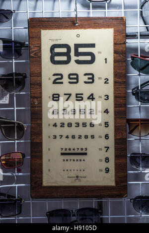 Eyesight test table with glasses over it hanging at the outdoor Thai market - Stock Photo
