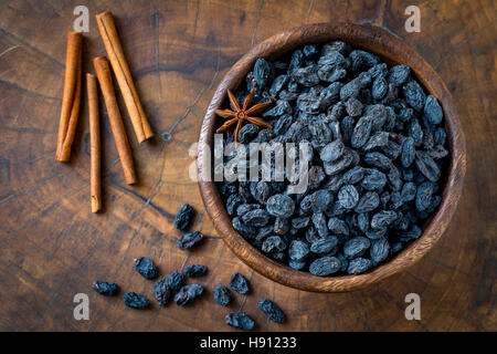 Black raisins and spices in wooden bowl. Top view, close up, horizontal - Stock Photo