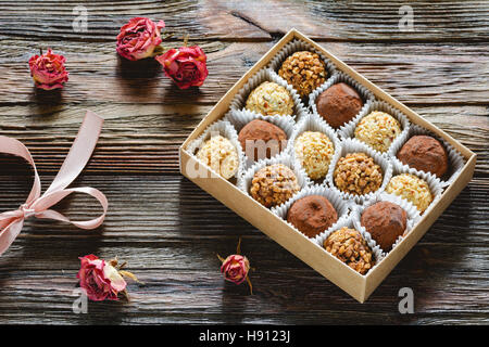 Box of delicious chocolates and pralines and dried pink roses. Valentine's day gift, Valentine day concept - Stock Photo