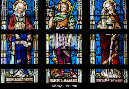 Stained Glass window depicting Saints Ana, Adrian and Barbara in the Church of Alsemberg, Belgium. - Stock Photo