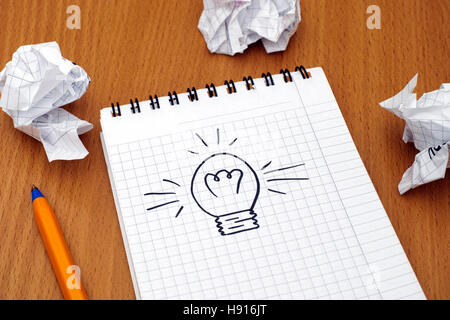 Light bulb drawn on white note pad with ballpoint pen and crumpled paper balls. - Stock Photo