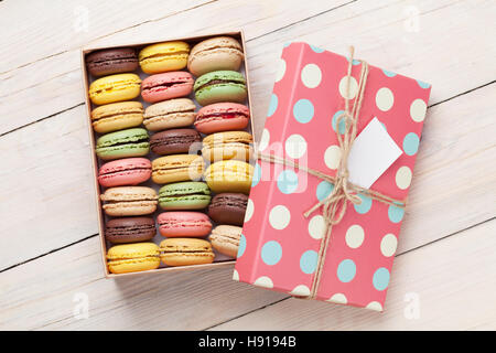 Colorful macaroons on wooden table. Sweet macarons in gift box. Top view - Stock Photo