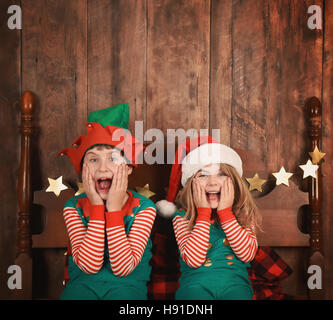 Two funny young children are surprised and excited sitting on a bed with Christmas pajamas with a wood wall. Use - Stock Photo