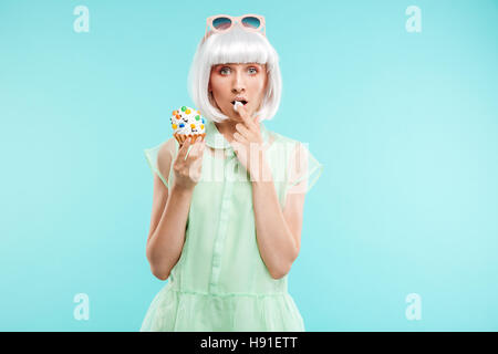 Pretty blonde young woman standing and tasting cupcake by finger over blue background - Stock Photo