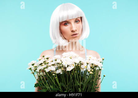 Pretty young woman in blonde wig holding bunch of flowers over blue background