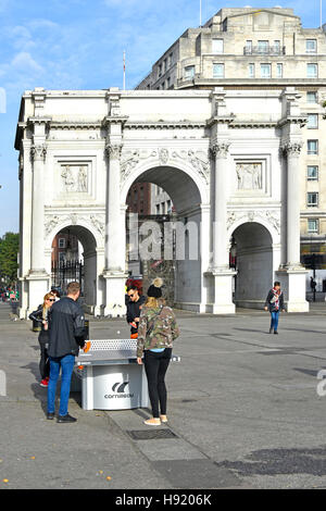 Table Tennis Ping Pong table tourists playing game on outdoor table in front of Marble Arch triumphal arch in London - Stock Photo