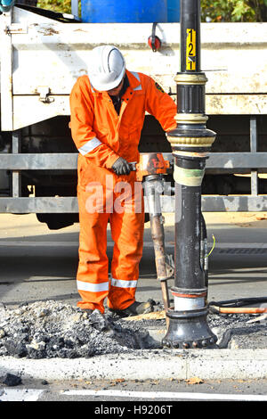 Workman working on road works repair job with compressed air jackhammer equipment tool breaking up around street - Stock Photo