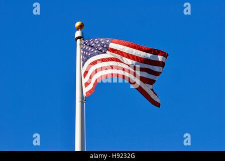 The flag of the United States of America on a flagpole blowing in a breeze against a clear, dark blue sky with room - Stock Photo