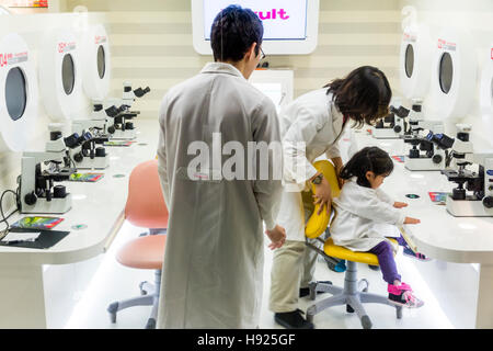 Japan, Nishinomiya, KidZania. 2 young child, girl, in white science coat  assisted by adult woman who is adjusting - Stock Photo