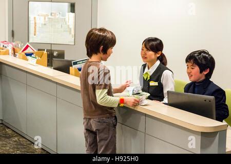 Japan, Nishinomiya, KidZania, child activity centre. Bank, interior, child, boy, withdrawing money from boy cashier - Stock Photo
