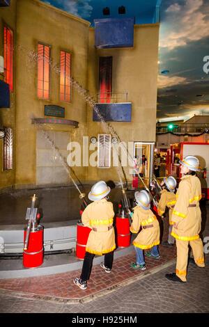 Japan, Nishinomiya, KidZania, Child activity play centre. Line of children dressed as firemen aiming hose pipes - Stock Photo