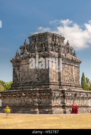 Monks walking around Candi Mendut a 9th century Buddhist Temple in Magelang near Yogyakarta in central Java in Indonesia. - Stock Photo