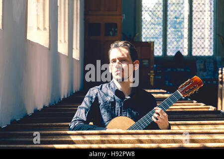 Young male classical musician with a guitar