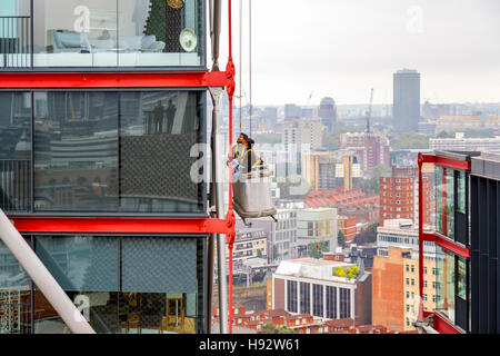 London, UK - September 20, 2016 - Window cleaners working on a high rise building with cityscape in the background - Stock Photo