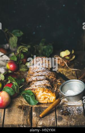 Apple strudel cake with cinnamon, sugar powder and fresh apples - Stock Photo