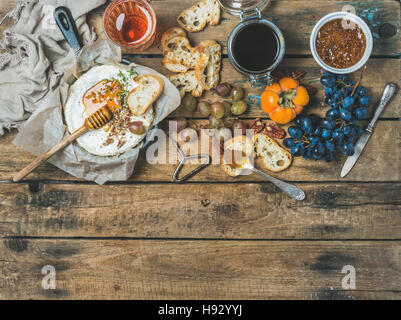 Camembert cheese, fruits, bread, honey, nuts, jam and rose wine - Stock Photo