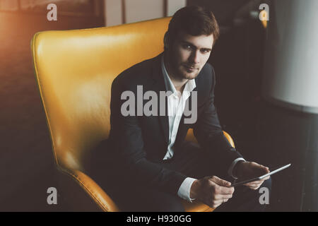 Young serious successful man entrepreneur in formal business suite with a beard sitting on yellow armchair with - Stock Photo