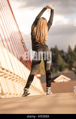 Beautiful woman stretching in yoga pants before her run - Stock Photo
