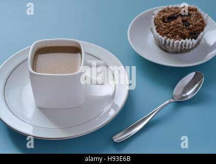 White square cup of coffee, silver spoon and brown fiber muffin set on blue table , viewed from slightly above - Stock Photo