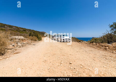CRETE, GREECE - JULY 11, 2016: Cars are on a dirt road. Peninsula Kalydon. - Stock Photo