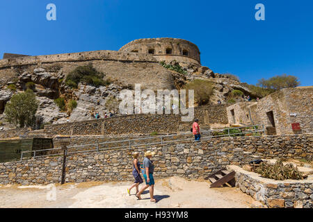 CRETE, GREECE - JULY 11, 2016: Tourists on Spinalonga island and fortress of the same name. View from the sea. - Stock Photo