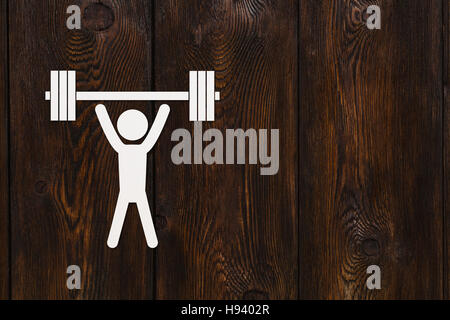 Paper man with weights. Sport, fitness concept. Copyspace, wooden background - Stock Photo