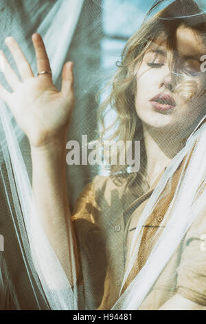 Beautiful young blond woman hand on blinds - Stock Photo