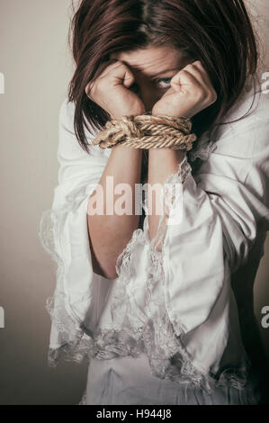 Female hostage  hands tired with rope - Stock Photo