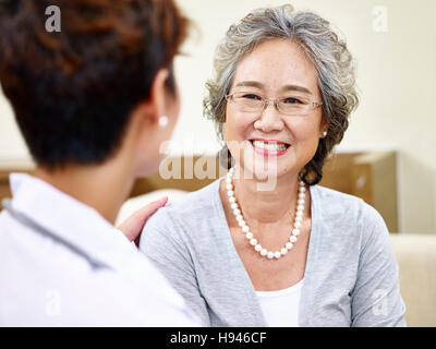 senior asian woman having a pleasant conversation with her family doctor, happy and smiling - Stock Photo